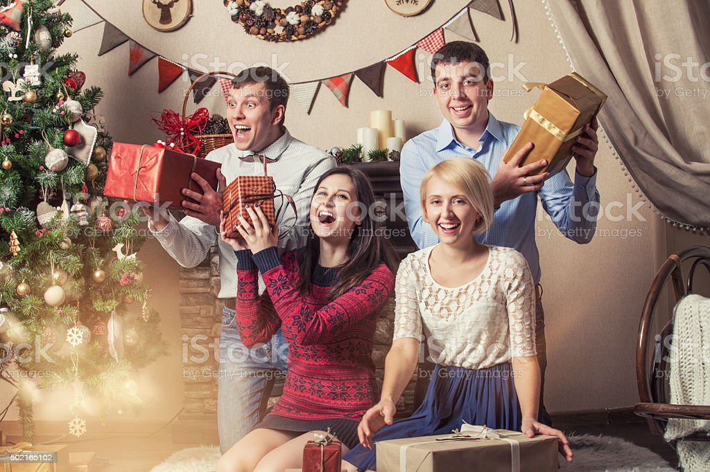 Friends of four men and women give gifts under the tree in the...