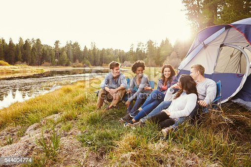 istock Friends on a camping trip relaxing by their tent near 544604774