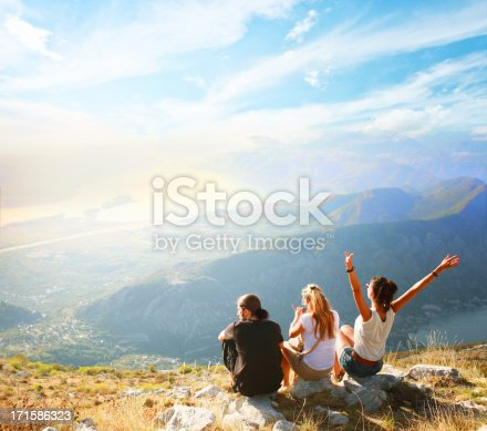 Three friends enjoying the amazing view on top of the mountain range, looking at the sea bay from above.