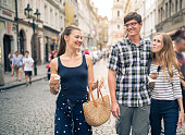 Group of young friends on a vacation, walking down the street eating local snacks