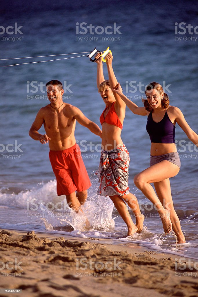 Friends on beach flying kite royalty-free stock photo
