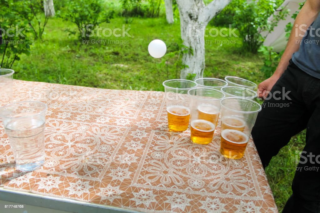 friends on birthday party playing beer pong game drinking alcohol stock photo