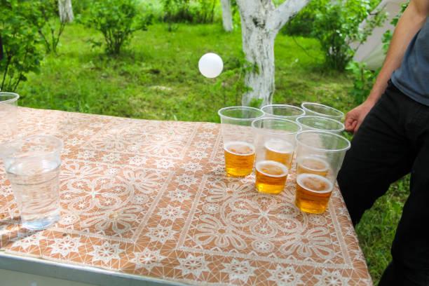 vrienden op de partij van de kindverjaardag spelen bier pong spel drinken van alcohol - beirut stockfoto's en -beelden