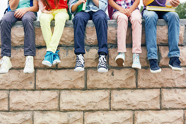 friends on brick wall - shoe stock photos and pictures