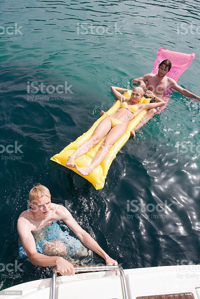 Friends on inflatable matresses in the sea royalty-free 스톡 사진