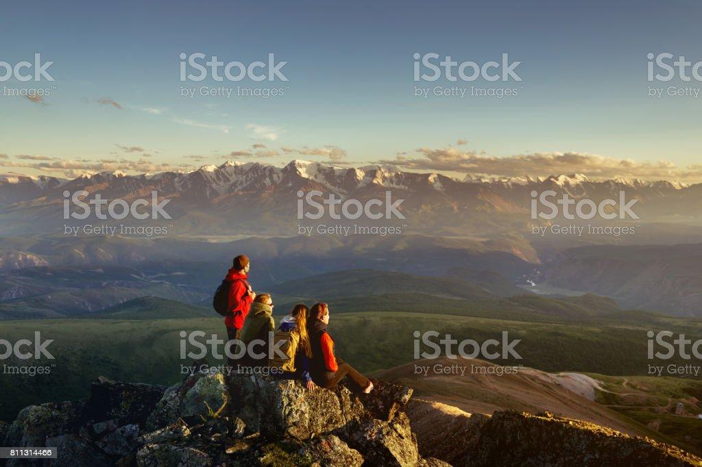 Amigos en la montaña mirando a la puesta del sol - foto de stock