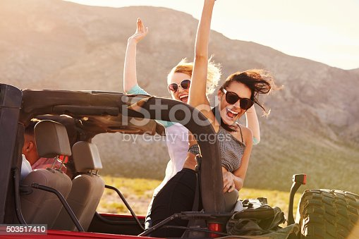 503545320istockphoto Friends On Road Trip Driving In Convertible Car 503517410