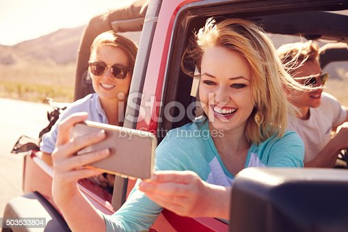503545320istockphoto Friends On Road Trip In Convertible Car Taking Selfie 503533804