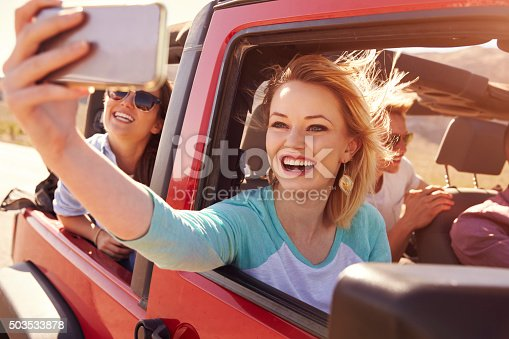 503545320istockphoto Friends On Road Trip In Convertible Car Taking Selfie 503533878