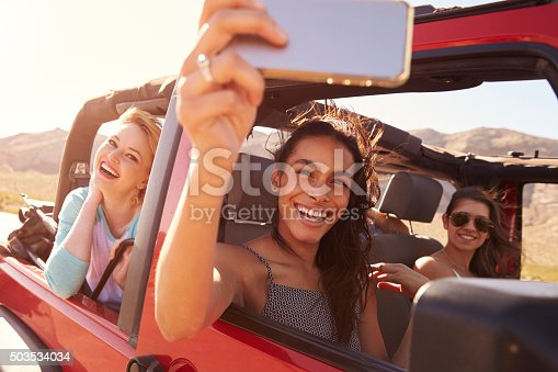 503545320istockphoto Friends On Road Trip In Convertible Car Taking Selfie 503534034
