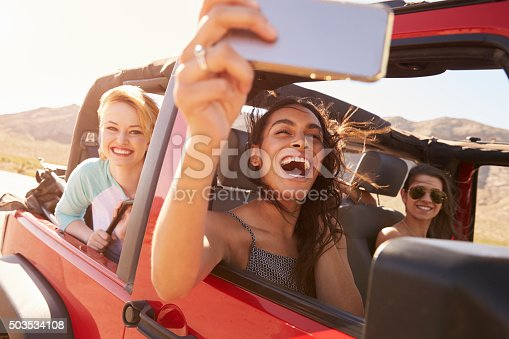 503545320istockphoto Friends On Road Trip In Convertible Car Taking Selfie 503534108