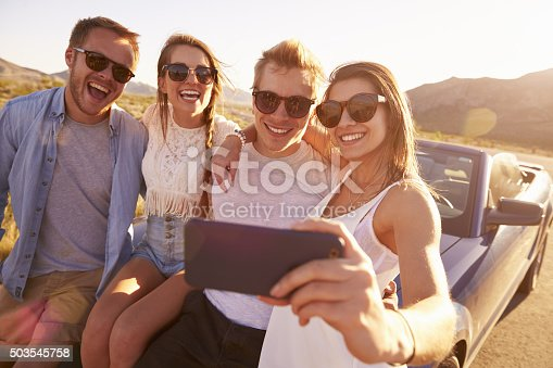 503545320istockphoto Friends On Road Trip Sit On Convertible Car Taking Selfie 503545758