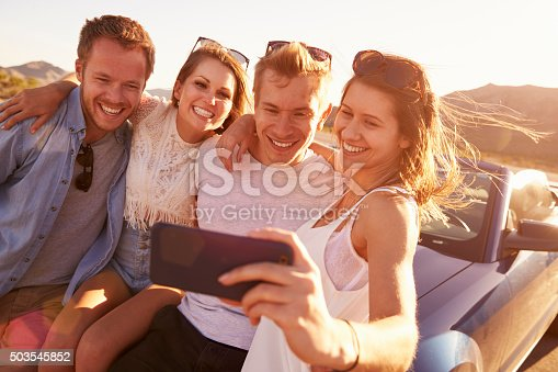 503545320istockphoto Friends On Road Trip Sit On Convertible Car Taking Selfie 503545852