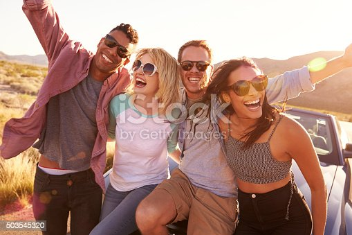 503545320istockphoto Friends On Road Trip Sitting On Hood Of Convertible Car 503545320