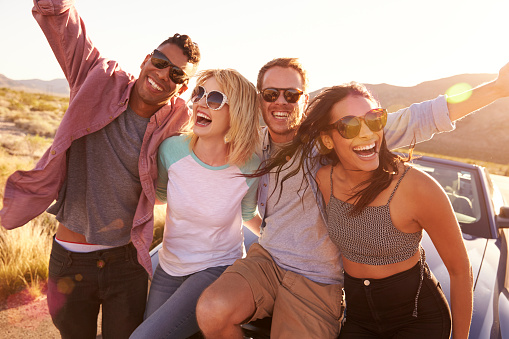 istock Friends On Road Trip Sitting On Hood Of Convertible Car 503545320