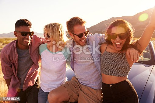 503545320istockphoto Friends On Road Trip Sitting On Hood Of Convertible Car 503545396