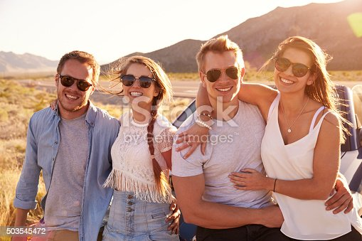 503545320istockphoto Friends On Road Trip Sitting On Hood Of Convertible Car 503545472