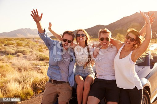 503545320istockphoto Friends On Road Trip Sitting On Hood Of Convertible Car 503545566