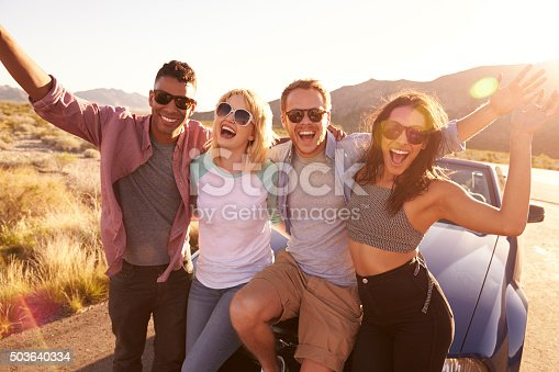 503545320istockphoto Friends On Road Trip Sitting On Hood Of Convertible Car 503640334