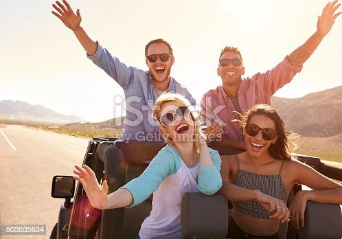 503545320istockphoto Friends On Road Trip Standing In Convertible Car 503535634