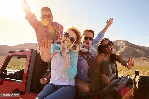 503545320istockphoto Friends On Road Trip Standing In Convertible Car 503535722