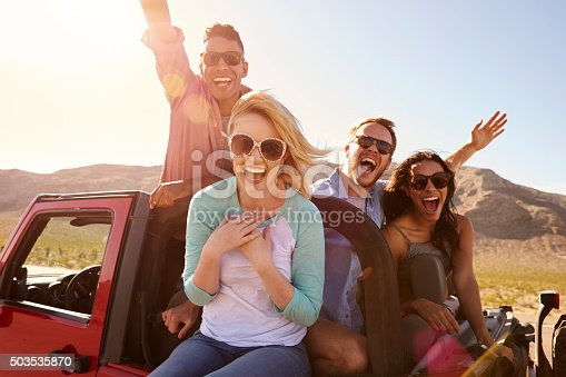 503545320istockphoto Friends On Road Trip Standing In Convertible Car 503535870