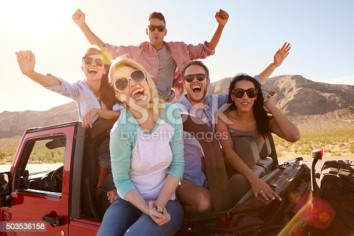 503545320istockphoto Friends On Road Trip Standing In Convertible Car 503536158