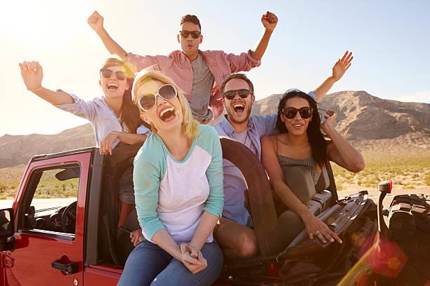 amis sur road trip debout en voiture décapotable - homme faire coucou voiture photos et images de collection
