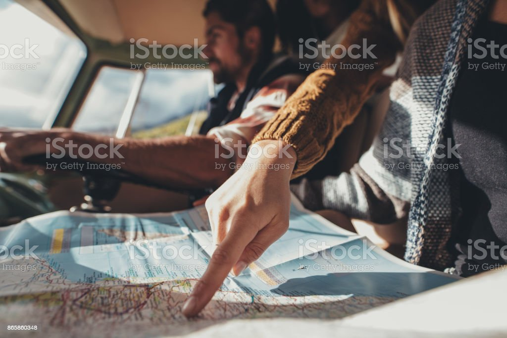 Friends on road trip using map for directions stock photo