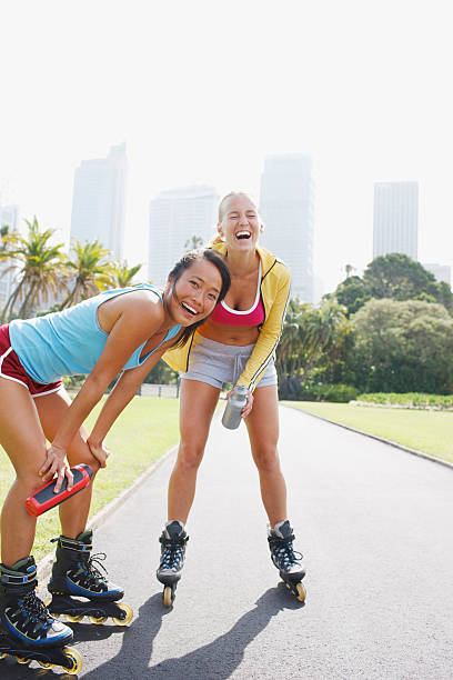 Friends on rollerblades on park stock photo
