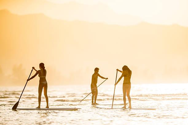 freunde auf dem stand-up-paddleboards (sup) - stehpaddeln stock-fotos und bilder