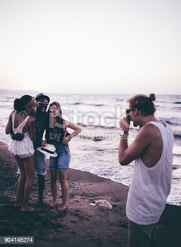 istock Friends on summer island holidays posing for photo on beach 904145274