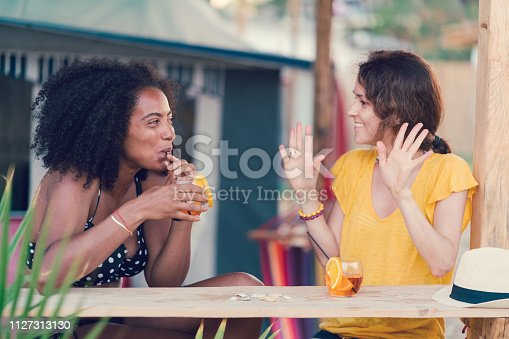 Girls sitting at the beach bar and drinking refreshing drinks