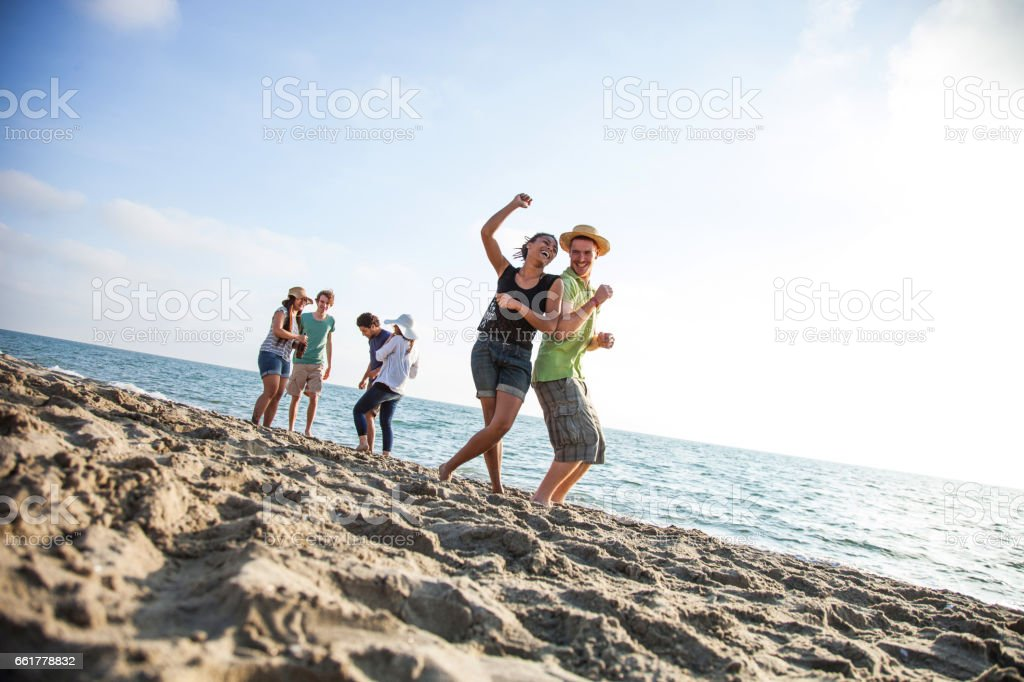 Friends on the beach during vacations stock photo