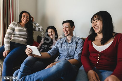 Friends on the couch watching videos on tablet
