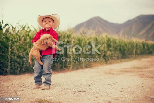 A young boy holds is golden retriever puppy while on the farm.