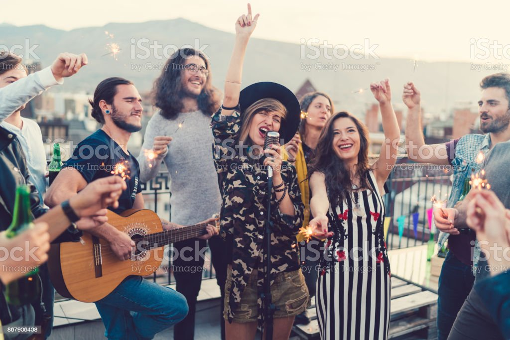 Friends on the rooftop listening to a guitar singer stock photo