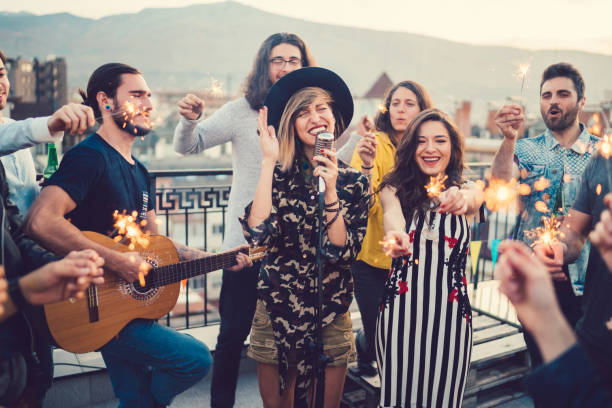 friends on the rooftop listening to a music band - young singles stock photos and pictures