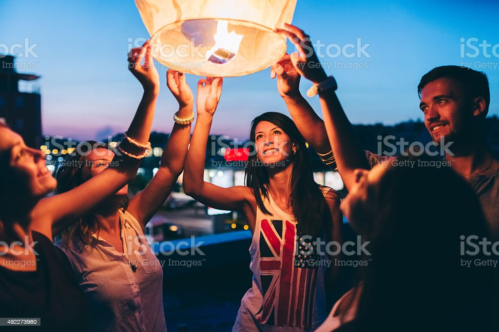 Friends on the rooftop releasing paper lantern stock photo