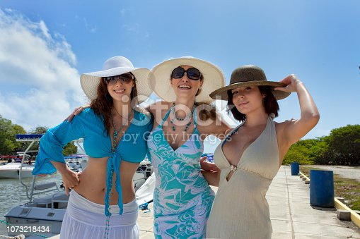 Three beautiful women with hats in a dock, about to board a ship. Friends on vacation. Horizontal composition portrait. Outdoors photography.