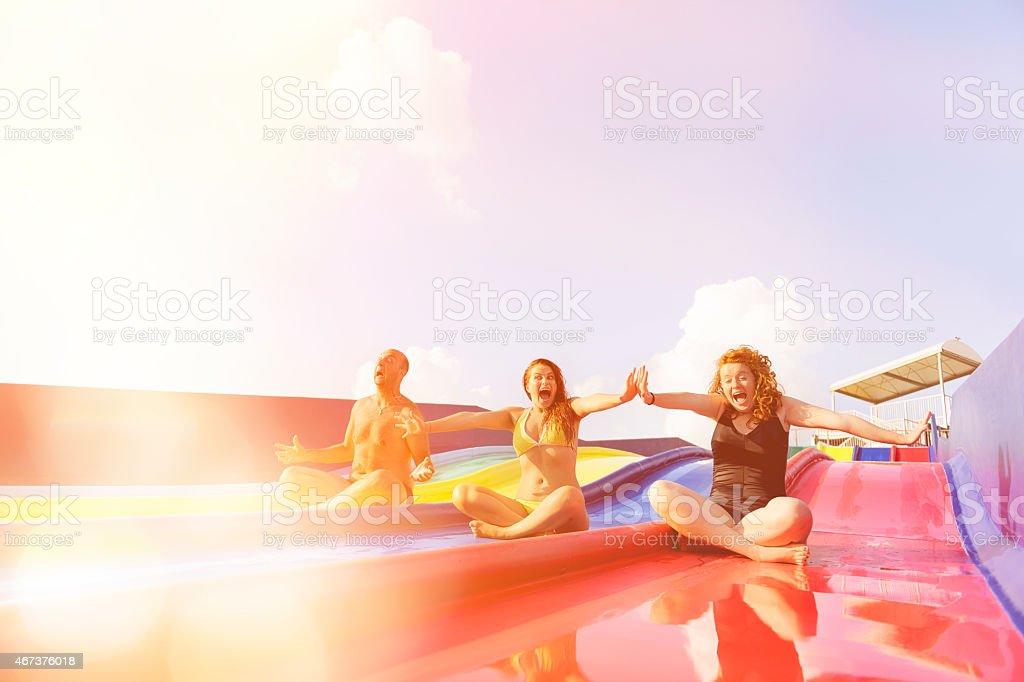 friends on water slide laughing stock photo