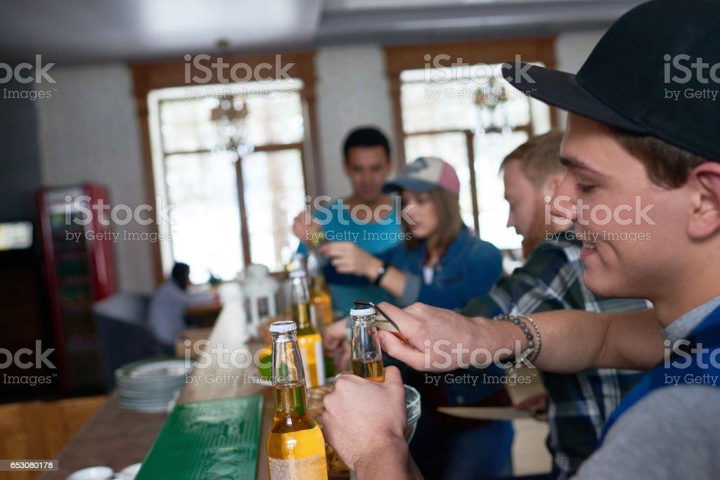 Friends opening beer bottles stock photo
