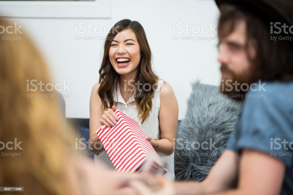 Friends opening Christmas presents stock photo