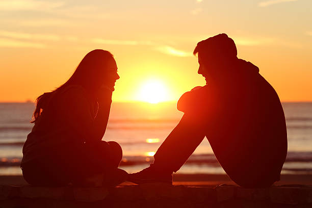 Friends or couple of teens facing at sunset Side view of full body of two friends or couple silhouette of teens facing at sunset on the beach with the sun in the middle love at first sight stock pictures, royalty-free photos & images