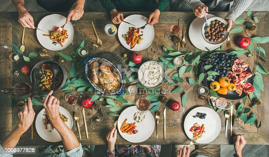 istock Friends or family eating at festive Christmas table, top view 1066977828