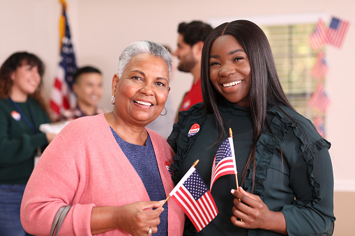 African descent mother, daughter or friends vote in the USA election.  They stand together holding flags and wearing