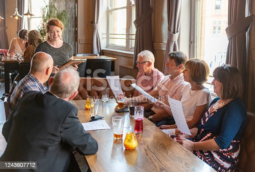 A group of mature men and women give their food orders to a waitress in a pub.
