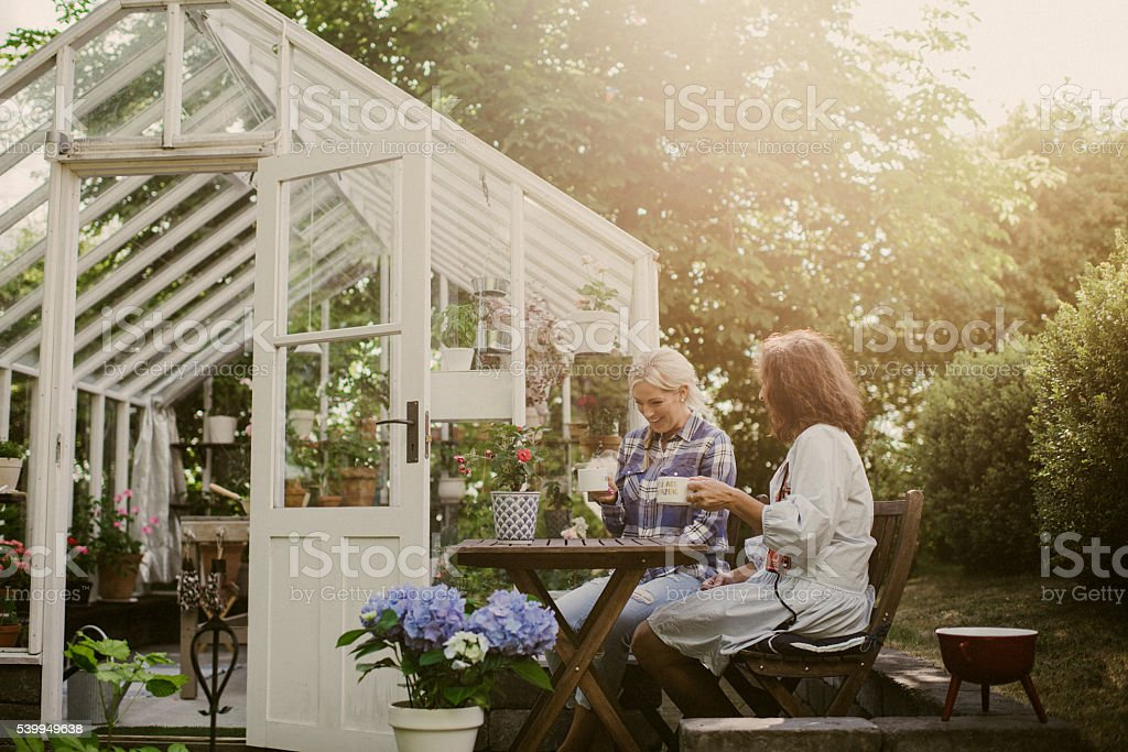 Friends outside greenhouse having coffee break stock photo