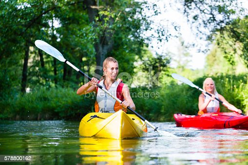 istock Friends paddling with canoe on forest river 578800162