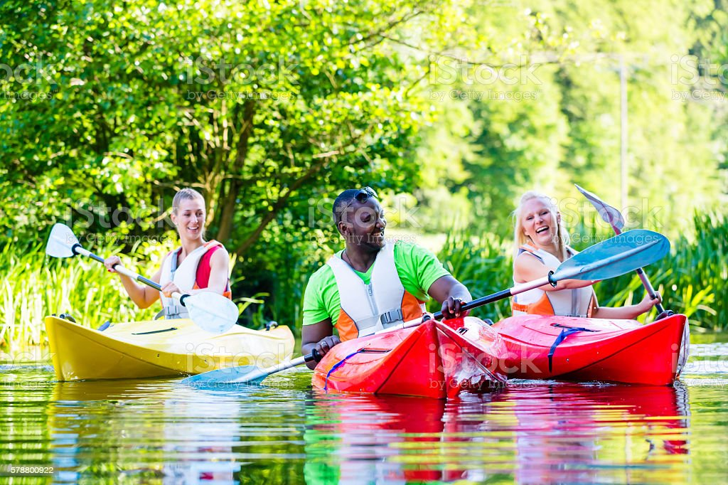 Friends paddling with canoe on forest river stock photo